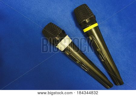 Two wireless microphones lie on a blue desk. Radio microphones for carrying out of an event and conferences close up. Soft focus. Modern technologies.