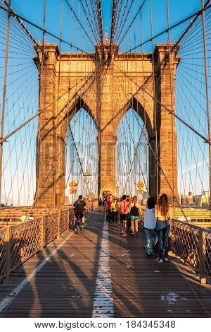 People walkway on the Brooklyn Bridge at sunset on June 26, 2016 in New York, NY. The Brooklyn Bridge is connects the Manhattan and Brooklyn by spanning the East River.