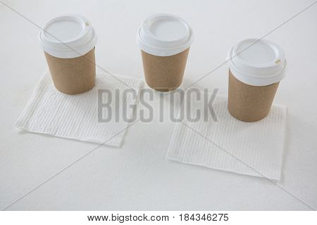 Disposable cups served with tissue papers on white background
