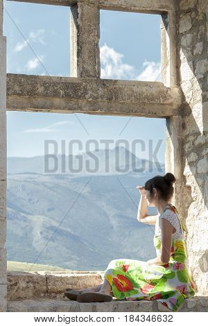 Back view of girl is covering her eyes from sun and looking ahead from window sill