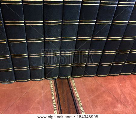 Row of old antique books on vintage desk
