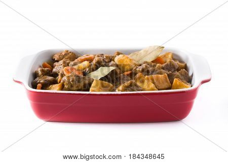 Beef meat stewed with potatoes, carrots and spices in ceramic pot isolated on white background