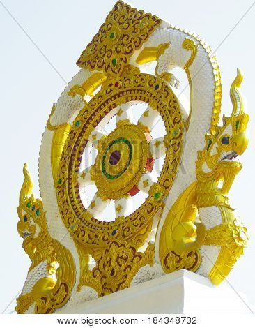 Gold and white masonry decoration with a center resembling a spoke wheel and gold dragons on either side on top of a Temple wall.