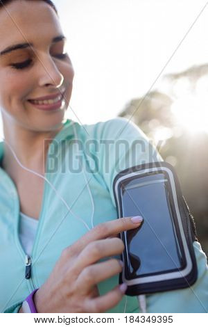 Female jogger listening to music on mobile phone in park