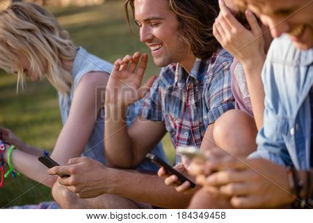 Friends text messaging on mobile phone in park on a sunny day