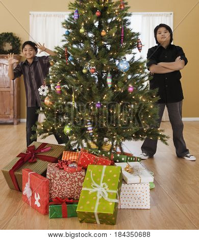 Filipino boys in living room with Christmas tree and gifts