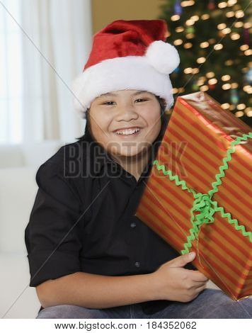 Filipino boy holding Christmas gift