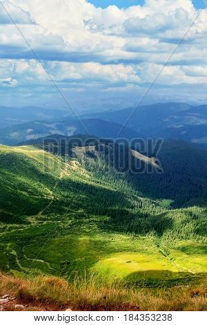 Summer mountain landscape. Mountain path. Landscape with mountains and green hills with blue sky and clouds. Carpathian Mountains, Europe.