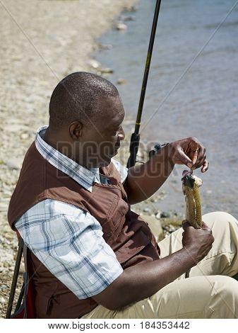 Black man removing fish from hook near stream