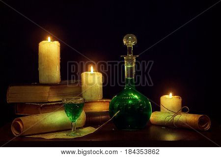 Magic potion, ancient books and candles. Old texture. Photo in  low key.