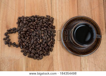 Cup of black coffee and coffee beans forming shape of cup on wooden background