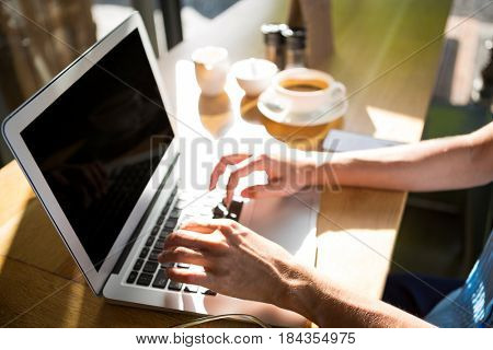 Hands of woman using laptop at café