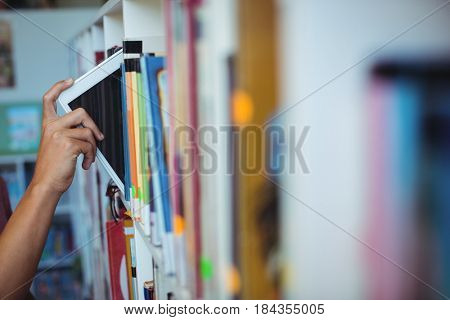 Hand of student keeping digital tablet in bookshelf in library at school