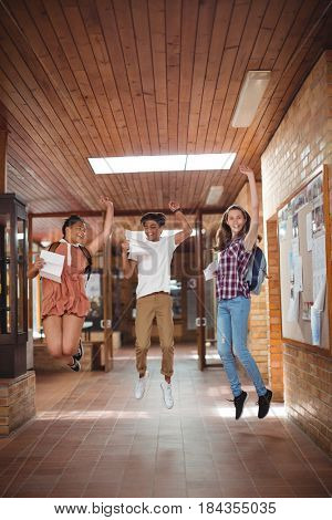 Excited classmates jumping with grade cards in corridor at school