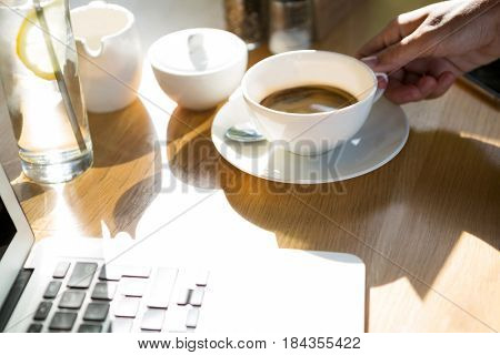Hand of woman holding coffee cup at café