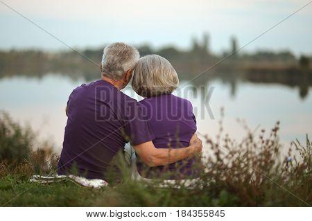 Happy senior couple sitting in summer near lake during sunset
