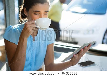 Female executive using digital tablet while having coffee at café