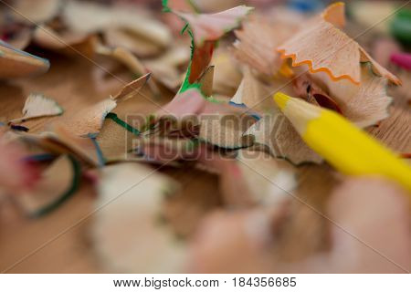 Colored pencil shavings with yellow pencil color on wooden background