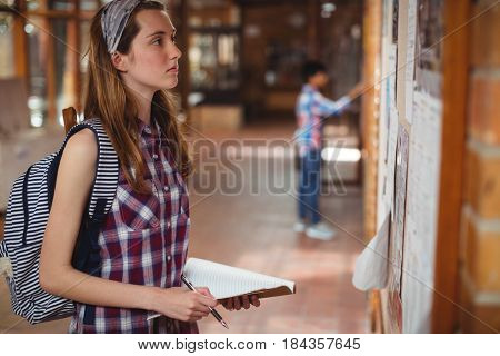Schoolgirl reading notice board in corridor at school