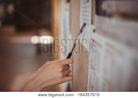 Schoolgirl looking at notice board in corridor at school