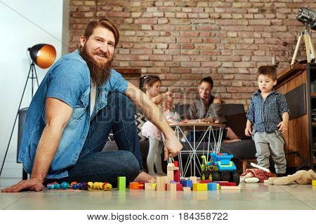 Happy family playing at home, father sitting on floor, smiling, looking at camera.