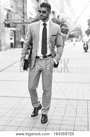 Successful dedicated young businessman walking on street in business district wearing suit tie and sunglasses holding suitcase.