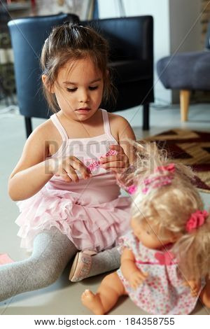 Little girl playing with doll at home on floor.