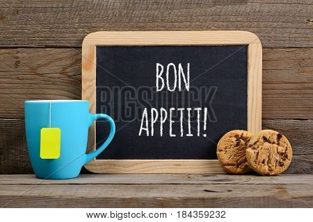 Wishes bon appetit on small blackboard cup of tea and cookies on wooden background