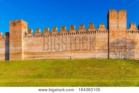 Brick wall and two watch towers in the city of Cittadella, it's a walled city in the province of Padua (Padova), Italy. Man walking on grass along the wall around the old town center