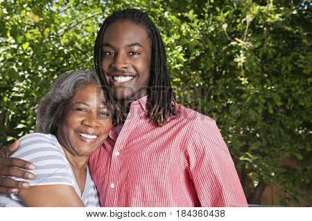 Black grandmother and grandson hugging outdoors