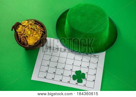 St. Patricks Day leprechaun hat with shamrock, calendar and pot with chocolate gold coins on green background