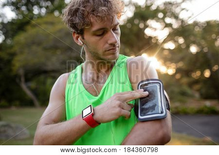 Male jogger listening to music on mobile phone in park