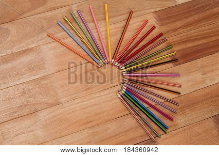 Colored pencils arranged in a semi-circle on wooden background