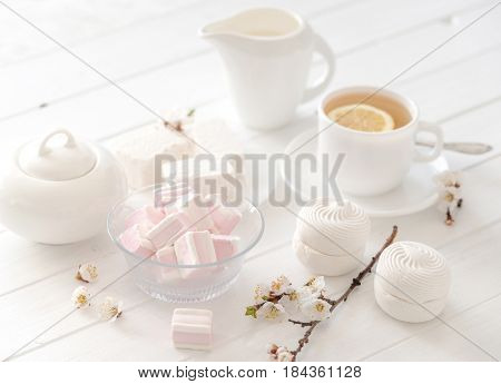 Pastel tea set with zefir and sweets, marshmellow and milk on side, decorated with flowers