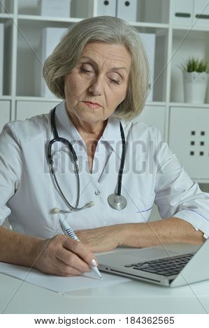 Old doctor with a laptop working in the office