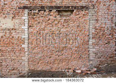 Close up obsolete weathered demolished red brick wall