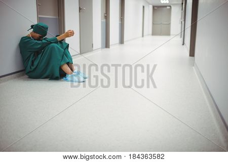 Tensed female surgeon sitting in corridor of hospital