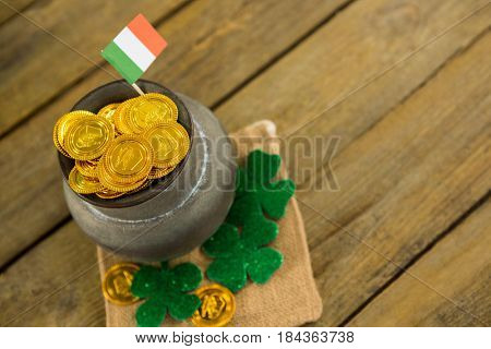St. Patricks Day shamrock, flag and pot filled with chocolate gold coins on wooden table