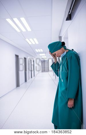 Tensed female surgeon standing in corridor of corridor