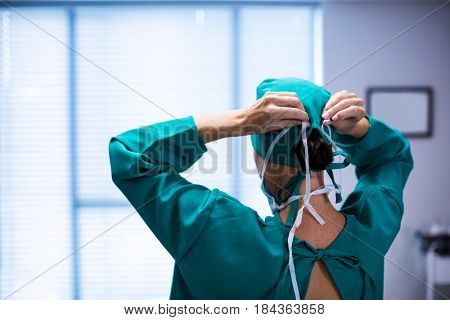 Rear view of female surgeon wearing surgical mask in operation theater of hospital