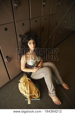 Middle Eastern teenager listening to music in locker room