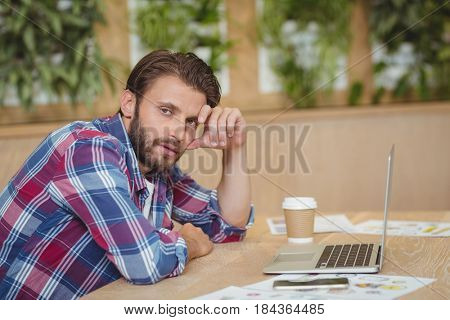 Portrait of tensed executive with laptop siting at desk in office