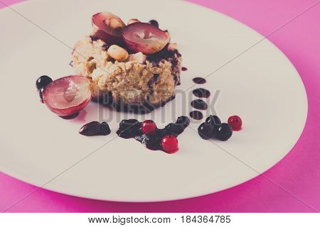 Healthy breakfast, dieting and detox concept - wholegrain fresh oatmeal porridge on plate with fruits, berries and nuts. Still life, shallow depth of field