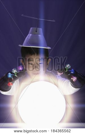 Korean boy in superhero costume looking at glowing orb