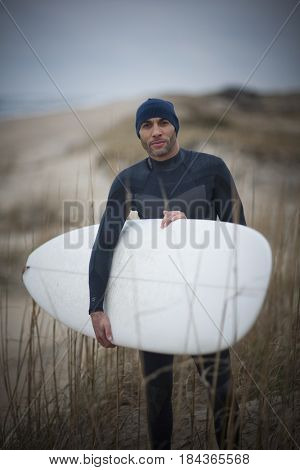 African American man in wet suit carrying surfboard
