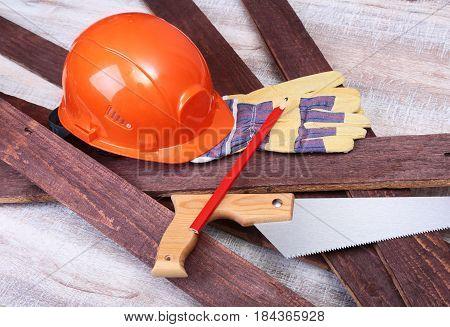 Orange hard hat, safety glasses, gloves and measuring tape for work on wooden background