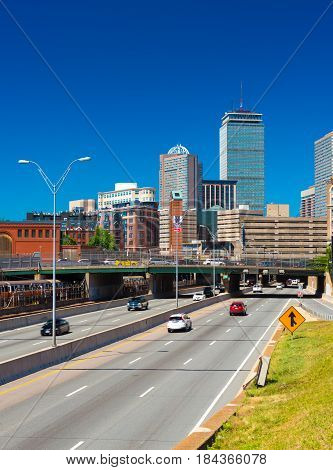 Boston, Massachusetts - June 2016, USA: Cityscape of Boston Back Bay against the clear blue sky, view of highway with traffic, Prudential Center and surrounding buildings