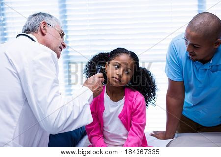 Doctor examining patients ear with otoscope in clinic