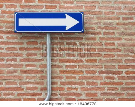 one way sign over a bricks wall