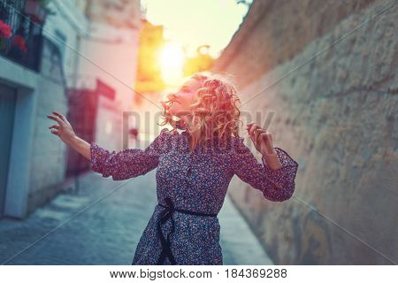 Happy carefree woman dancing on street in sunset